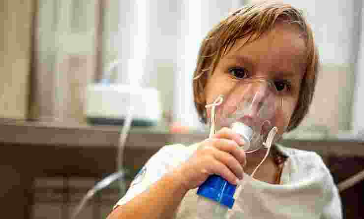 Young child holding breathing apparatus over nose and mouth